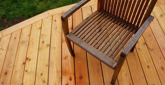 Holzterrasse auf Rasenflaeche mit Holstuhl